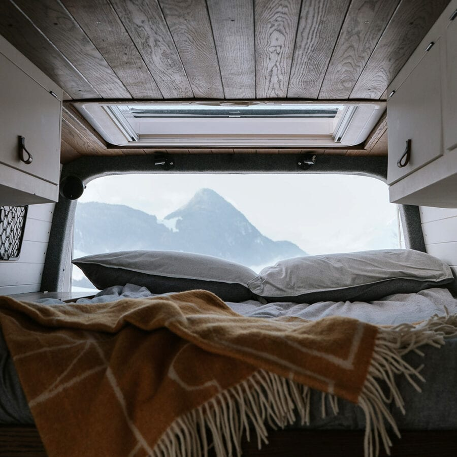 Inside of a campervan looking out over the mountains in winter